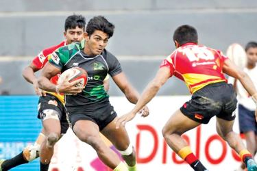 Etisalat Panthers' Naveen Heenakankanamge (ball in hand) making a break against Cargils Gladiators defenders during the Shield battle of the first leg of the Sri Lanka Rugby Super Sevens 2017.