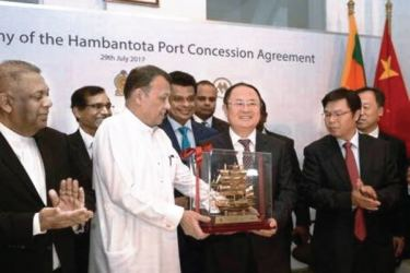 Minister of Ports and Shipping Mahinda Samarasinghe (centre) exchanges souvenirs with Executive Vice President of China Merchants Port Holdings Dr. Hu Jianhua (third right) during the Hambantota International Port Concession Agreement at a signing ceremony in Colombo on July 29.  AFP