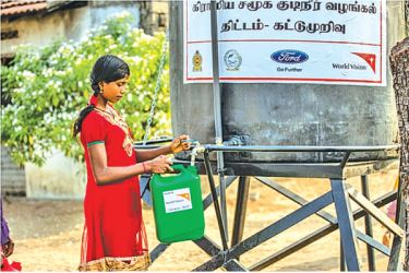 A Kattumurivu Villager collects her precious quota of safe and clean drinking water from the community tap.