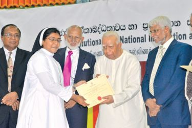 A memento being handed over to a participant by Opposition Leader R. Sampanthan.