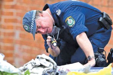 An Australian Police officer searches items seized from a property during a raid in the Sydney suburb of Lakemba, Australia. - AFP