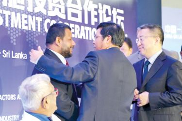 Minister Bathiudeen (left), Chinese Ambassador Yi Xianliang (centre) and Chairman of the China International Contractors Association Fang Qiuchen (right) greet each other