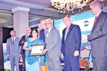 Richard Howitt, Chief Executive Officer, International Integrated Reporting Council and Wasantha Deshapriya, Secretary of the Ministry of Telecommunication and Digital Infrastructure handing over the award to Anusha Gallage, Chief Financial Officer of HNB