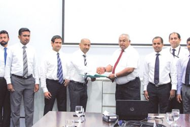 Officials from DIMO and Vallibel Finance exchanging the agreement
