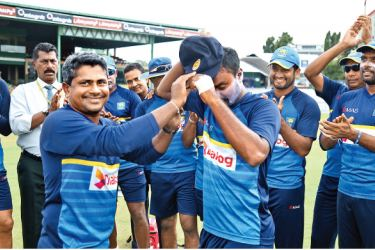 Malinda Pushpakumara receives his Test cap from veteran spinner Rangana Herath prior to the start of the second cricket Test between Sri Lanka and India at the SSC grounds yesterday. Pic by Nathan Delight