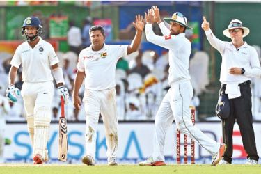 Sri Lankans Rangana Herath and Dinesh Chandimal celebrate the run out of Indian opener Lokesh Rahul for 57 on the first day of the second Test at the SSC grounds. – AFP