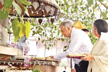 A Bodhi Pooja was held at the Parliamentary Complex yesterday to invoke blessings on Prime Minister Ranil Wickremesinghe who completed 40 years in Parliament. Picture shows Prime Minister Ranil Wickremesinghe and his wife Prof. Maithri Wickremesinghe making offerings to the Buddha statue. Picture by Thilak Perera