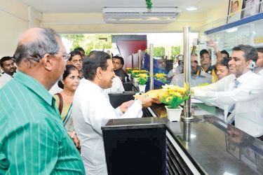 Health Minister Dr. Rajitha Senaratne hands over the drugs for the first prescription brought to the newly opened SPC outlet at Anuradhapura. Women and Child Affairs Minister Chandrani Bandara and others look on.