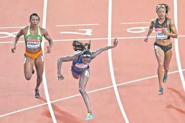 US athlete Torie Bowie crosses the finish line next to Ivory Coasts Murielle Aohoure (left) and Jamaica's Elaine Thompson to win the women's 100 metres final at the World Athletics Championships in London. AFP