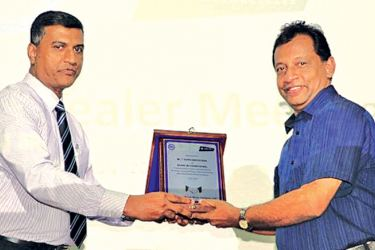 Rohana Dissanayake, DPMC Director and Chief Operating Officer presenting an award of appreciation to a long-standing dealer