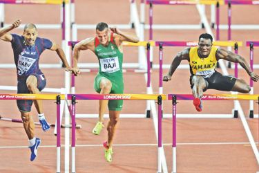 Jamaica's Omar Mcleod (R) clears the final flight during the final of the men's 110m hurdles athletics event at the 2017 IAAF World Championships at the London Stadium in London on August 7. AFP