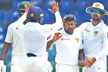 Rangana Herath mobbed by his team mates will sit out the third Test against India at Pallekele. AFP
