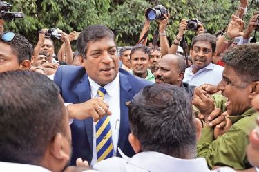 Ravi Karuananayke greets his supporters adorned with the tie of his Alma Mater after  returning from Parliament, where he resigned as Minister of Foreign Affairs yesterday. Picture by Rukmal Gamage