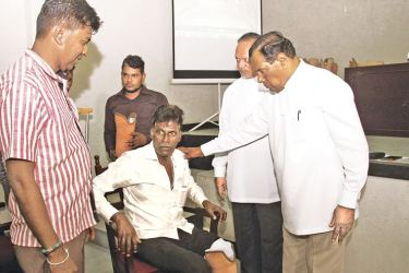 Labour  and Trade Union Relations Minister W.D.J. Seneviratne with one of the  recipients of an artificial limb. Labour and trade Union Relations State  Minister Ravindra Samaraweera looks on.