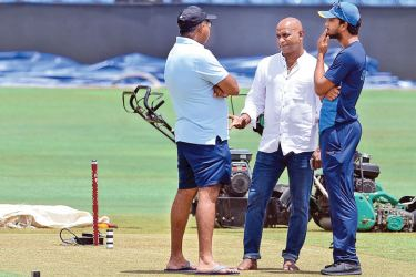 Sri Lanka Test captain Dinesh Chandimal chats with cricket manager and selector Asanka Gurusinha and selection committee chairman Sanath Jayasuriya at the Pallekele International Stadium yesterday, venue of the third and final Test against India. AFP