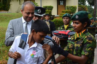 Children of STF personnel who made supreme sacrifice for the nation's sovereignty and territorial integrity received stationery at the  ceremony. Picture shows a child receives a bag of stationery from Law  and Order and Souther Development Minister Sagala Ratnayake.  Picture by  Sarath Peiris