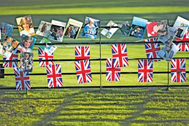 Union Flag bunting and photographs are seen on a railing outside the gates of Kensington Palace in London on August 31, 2017, to mark the 20th anniversary of the death of Diana,  Princess of Wales