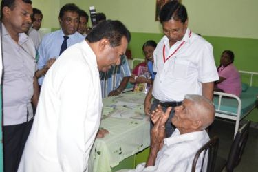 Social Empowerment and Welfare Minister S. B. Dissanayake talking to a patient while HelpAge Executive Director Samantha Liyanawaduge looks on.