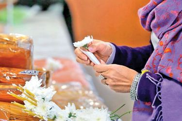 A woman offers flowers and robe cloth at Wat Velouvanaram, a Buddhist temple in Seine-et-Marne, France.