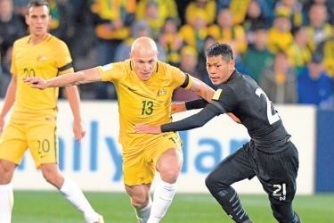 Aaron Mooy of Australia (C) fends off Pokklaw A-Nan of Thailand (R) during the World Cup 2018 qualifying football match between Australia and Thailand in Melbourne on September 5. AFP