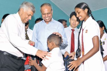 Prime Minister, Ranil Wickremesinghe, Minister of Law and Order and Southern Development, Sagala Ratnayaka, Huawei Sri Lanka CEO Shunli Wang handing over a donations to a student.