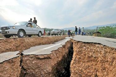 Residents gather as they inspect large cracks on a road after the earthquake.