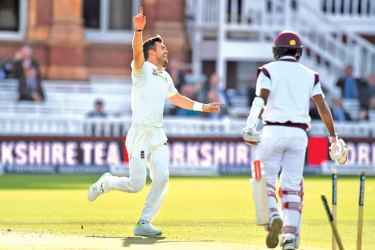 England's James Anderson (L) celebrates after taking his 500th Test match wicket, West Indies' Kraigg Brathwaite (R) for 4 runs, during the second day of the third international Test match between England and West Indies at Lords cricket ground.