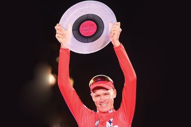 """Team Sky's British cyclist Chris Froome raises his trophy as he celebrates on the podium winning the 72nd edition of """"La Vuelta"""" Tour of Spain cycling race, in Madrid, on September 10. AFP"""