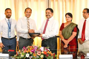Commercial Bank's Executive Director,Chief Operating Officer S. Renganathan and DIMO's Executive Director  Vijitha Bandara exchange the agreement in the presence of senior management of the two companies.