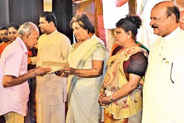 Former President Chandrika Bandaranaike Kumaratunga handing over a title deed to a beneficiary. Picture by J. Mohamed Hafees, Akurana Group Corr
