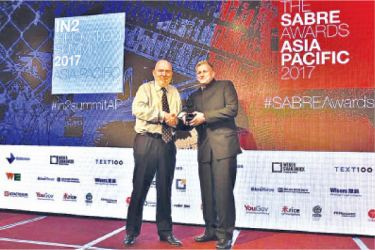 On behalf of Ogilvy Public Relations Sri Lanka, Scott Kronick,  Ogilvy PR's President and CEO for Asia Pacific (right), accepts the  Platinum 'Best in Show' Award from Paul Holmes, Founder and Chairman of  the SABRE Awards