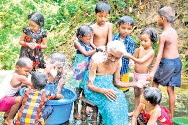 A group of children washing an elderly woman.  Picture by Sudath Pubudu Keerthi, Delgoda Group Corr.