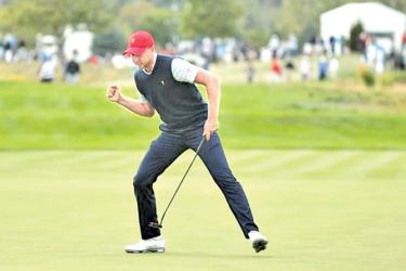 Daniel Berger reacts after making a putt on the 16th hole during the fourth round four-ball matches of The President's Cup golf tournament at Liberty National Golf Course.