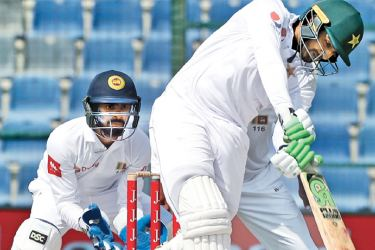Pakistan debutant Haris Sohail who scored a half-century to frustrate Sri Lanka plays an  on drive watched by wicket-keeper Niroshan Dickwella on the fourth day of the first Test at Abu Dhabi on Sunday. - AFP