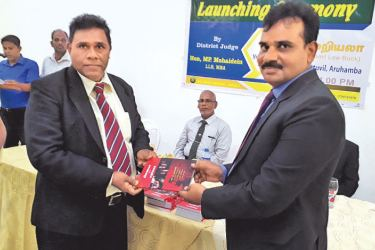 The ceremonial launch of a law book titled 'Pinaya Vilakkamariyala?' ('Bail or remand?') Authored by Batticaloa District Judge MP Mohideen, was held at the Auditorium of the Blue Wave Hotel in Arugam Bay on Sunday, with the participation of a large number of law professionals. Here, Trincomalee Additional District Judge/Magistrate M. H. M. Hamza receiving a copy of the book from Judge Mohideen. Picture by M. A. Phakurdeen, Addalaichenai Group Corr.