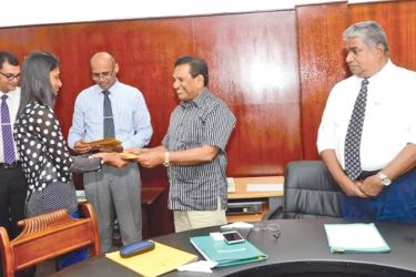 Health Minister Dr. Rajitha Senaratne handing over a scholarship to a student, while Deputy Health Minister Faizal Cassim and officials look on.