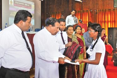 Labour and Trade Union Relations Minister W.D.J. Seneviratne hands over a scholarship to a student.
