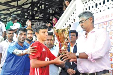 Minister Faiszer Musthapha presenting a trophy to a child at the ceremony.