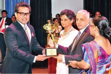 An Bio Extract official receiving the award from Minister of Development Strategies and International Trade Malik Samarawickrama.