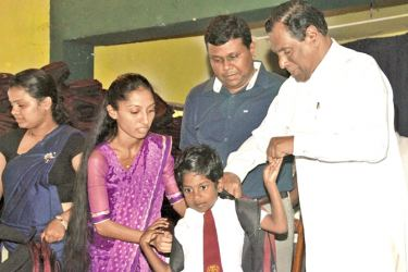 Labour and Trade Union Relations Minister W. D. J. Seneviratne hands over a set of school instruments to a student.