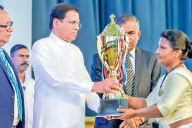 President Maithripala Sirisena  presenting a trophy to a postal worker. Picture by Udesh Gunaratne, President Media Unit