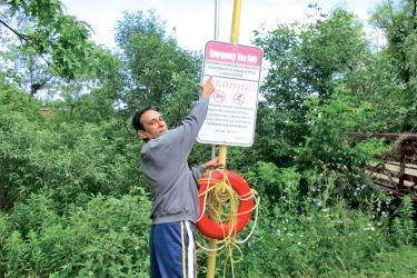 "The above sign board fixed at Brampton Loafer's Park of Ontario is associated with the proper use of the red inflated tube below. The clear warning writes: ""Anyone found misusing this equipment is subject to CAD $ 2000/= fine"". Approximately Rs.250, 000/=."