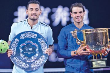 Rafael Nadal of Spain (R) holds the trophy after winning the men's singles final match against Nick Kyrgios (L) of Australia at the China Open tennis tournament in Beijing on October 8. AFP
