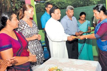 Health Minister Dr. Rajitha Senaratne hands over an appointment letter to a teacher who looks after children with special needs while others look on.