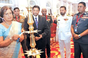 Former President Chandrika Bandaranaike Kumaratunga lighting the oil lamp while Navy Commander Vice Admiral Travis Sinniah, Defence State Minister Ruwan Wijewardene and other participants look on.