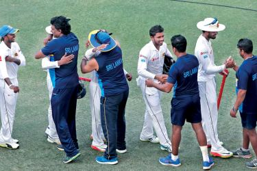 Sri Lanka players are congratulated by their support staff after their win over Pakistan in the second Test at Dubai International Stadium on Tuesday. – AFP