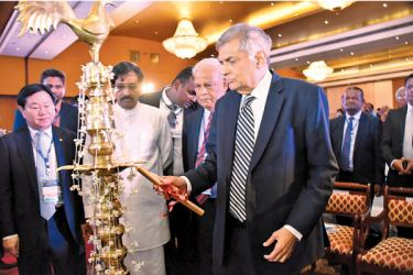 Prime Minister Ranil Wickremesinghe and Dr. P. A. Kiriwandeniya, Chairman of SANASA lighting the traditional oil lamp.