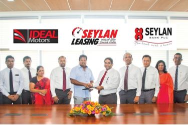 Kapila Ariyaratne, Director and Chief Executive Officer Seylan Bank exchanging the MoU with Nalin Welgama, Chairman of Ideal Motors, Flanked by Ideal Motors officials  and Seylan Bank officials.
