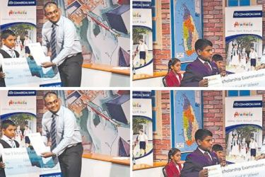 Commercial Bank's Deputy General Manager Marketing Hasrath Munasinghe presents the cash prizes to the four students placed first, second and third at the 2017 scholarship examination.