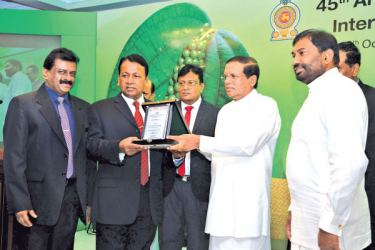 President Maithripala Sirisena presenting an award to one of the winners. Minister of Primary Industries Daya Gamage looks on. Picture by Sudath Malaweera